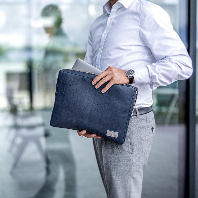 Business Geschäftsmann holt sein Tablet aus dunkelblauer LUCA Laptophülle aus Kork von Jorge Carmo
